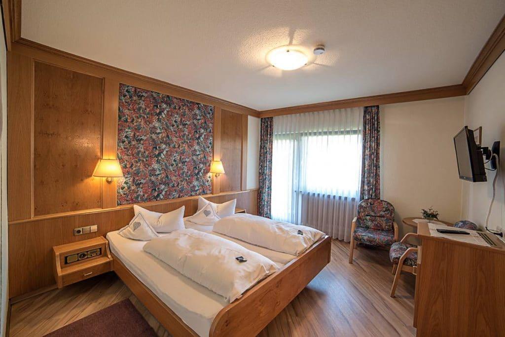 Großes Schlafzimmer mit Doppelbett, Schreibtisch, Sitzecke und Flachbild-SAT-TV