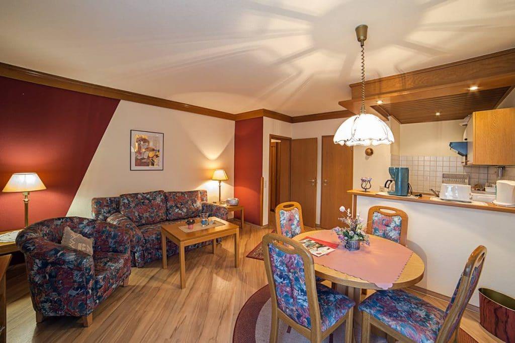 Große Wohnküche mit Esstisch und Couchecke und Küchentheke