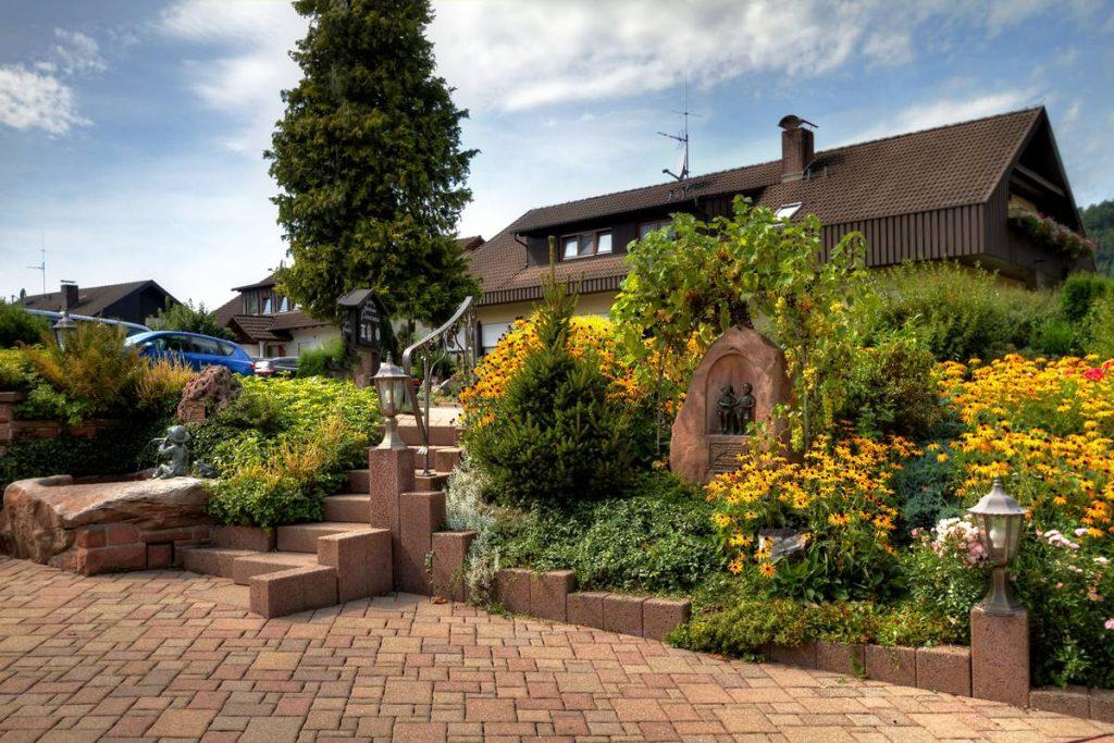 Sommerblumen vor dem Landhaus mit dem Gästehaus Panorama im Hintergrund