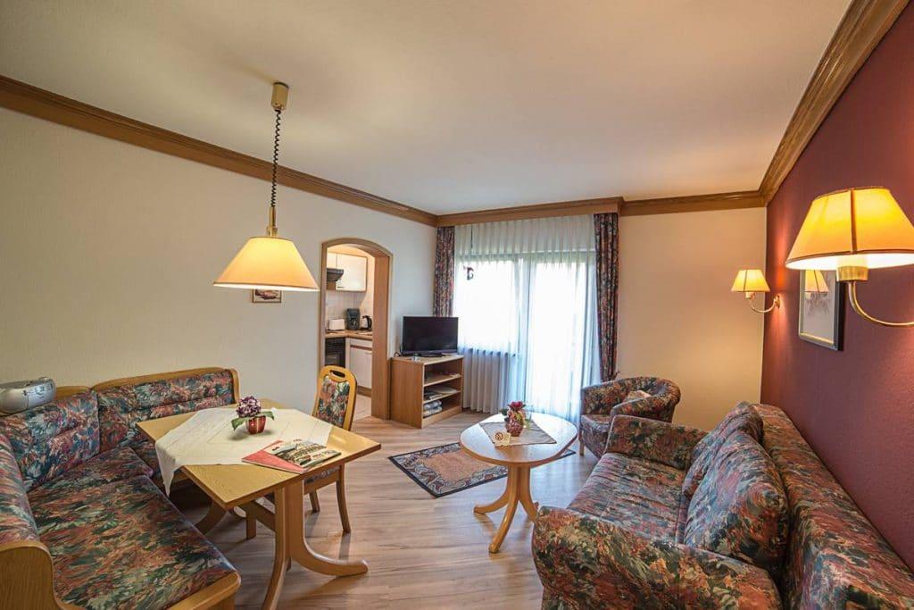 Wohnzimmer mit Flachbild-SAT-TV, Eckbank, Couchecke und Balkon