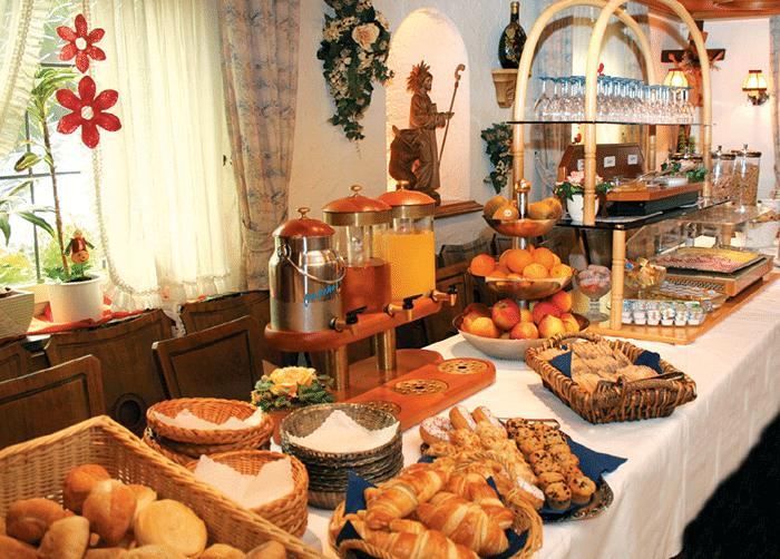 Frühstücksbuffet mit Saftkanne, Milchkanne, Brötchen, Croissants und Obst