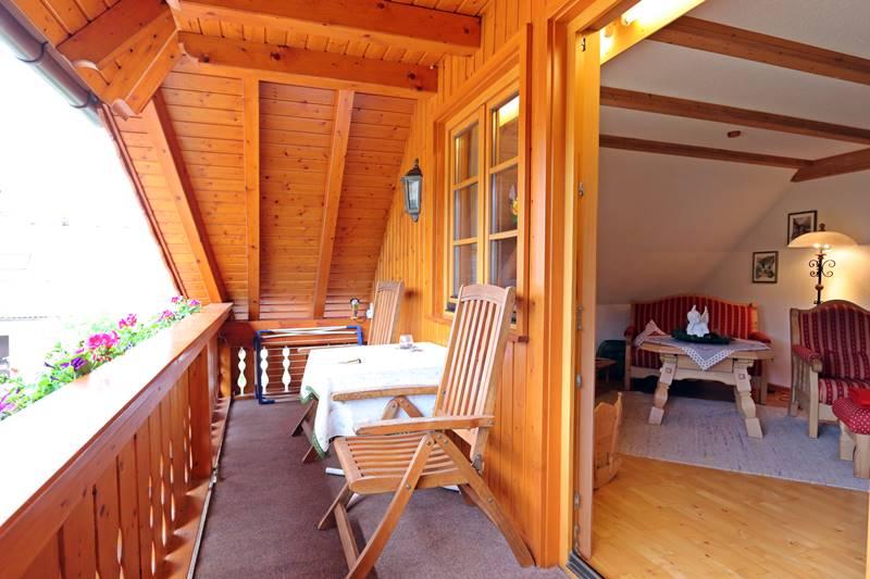 Balkon mit Blick ins Wohnzimmer der Ferienwohnung