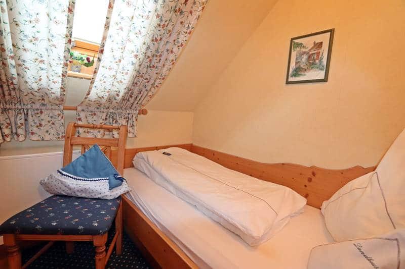 Einzelzimmer mit Stuhl und Dachfenster