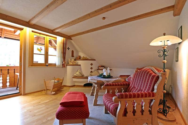 Wohnzimmer mit Kachelofen und Balkon in der Ferienwohnung Landhaus