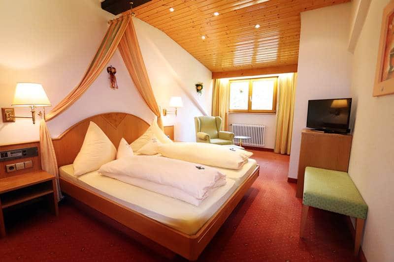 Doppelzimmer mit Himmelbett, Ohrensessel und TV