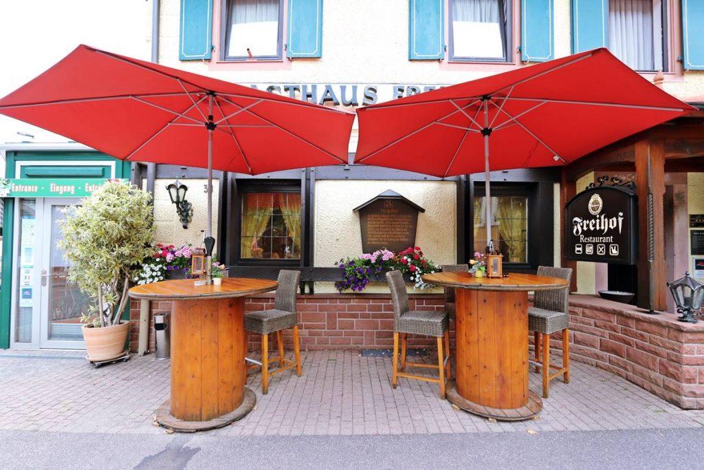 Stehtische aus Kabeltrommeln mit Sonnenschirm vor dem Hotel Freihof