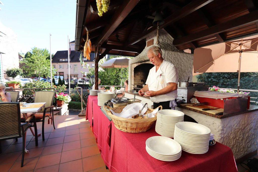 Michael Pfundstein vor dem Grill auf der Terrasse beim Vorbereiten des Grillabends