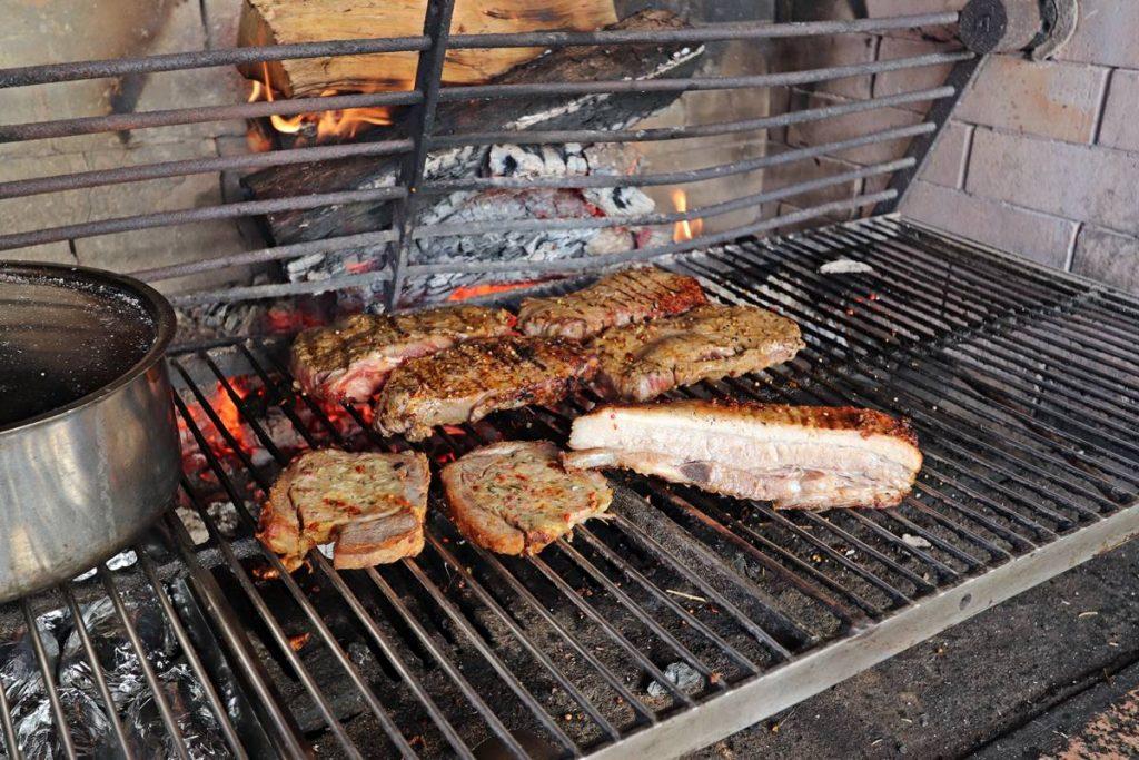 Schweinebauch, Rumpsteak und gefüllter Schweinebauch auf dem Rost des Grills