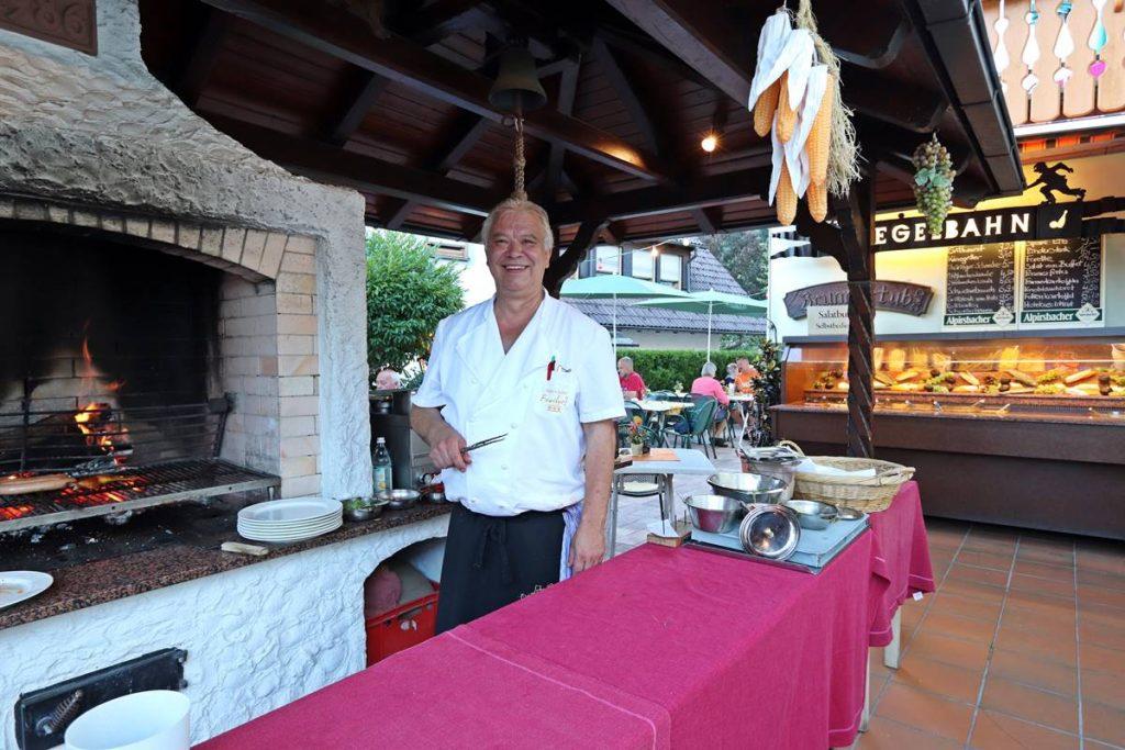 Hotelchef Michael mit Fleischgabel vor dem Grill auf der Terrasse