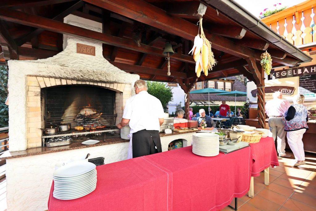 Chef Michael Pfundstein vor dem Grill auf der Terrasse von Hotel Freihof