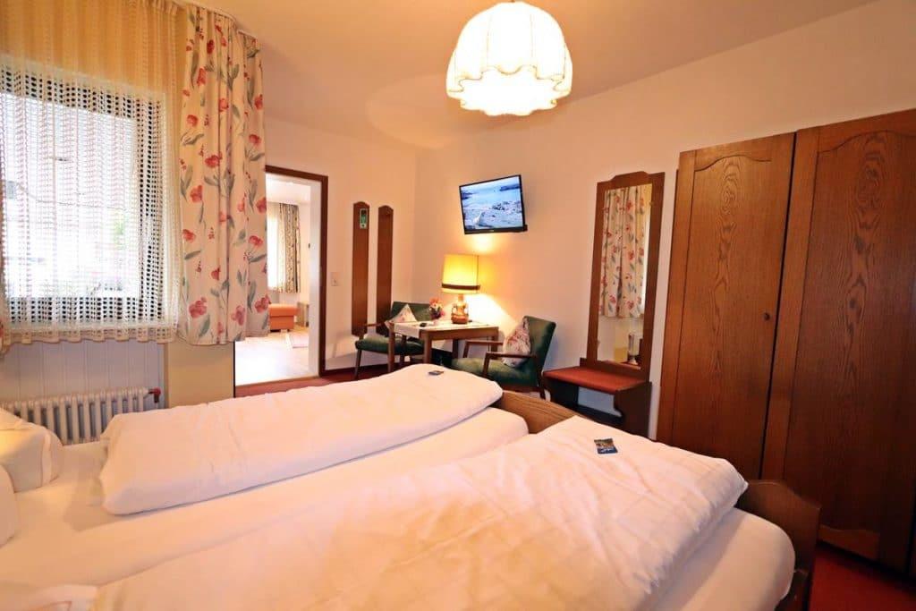 Schlafzimmer mit Flachbild-SAT-TV der Ferienwohnung Rosalie im Gästehaus Romantika