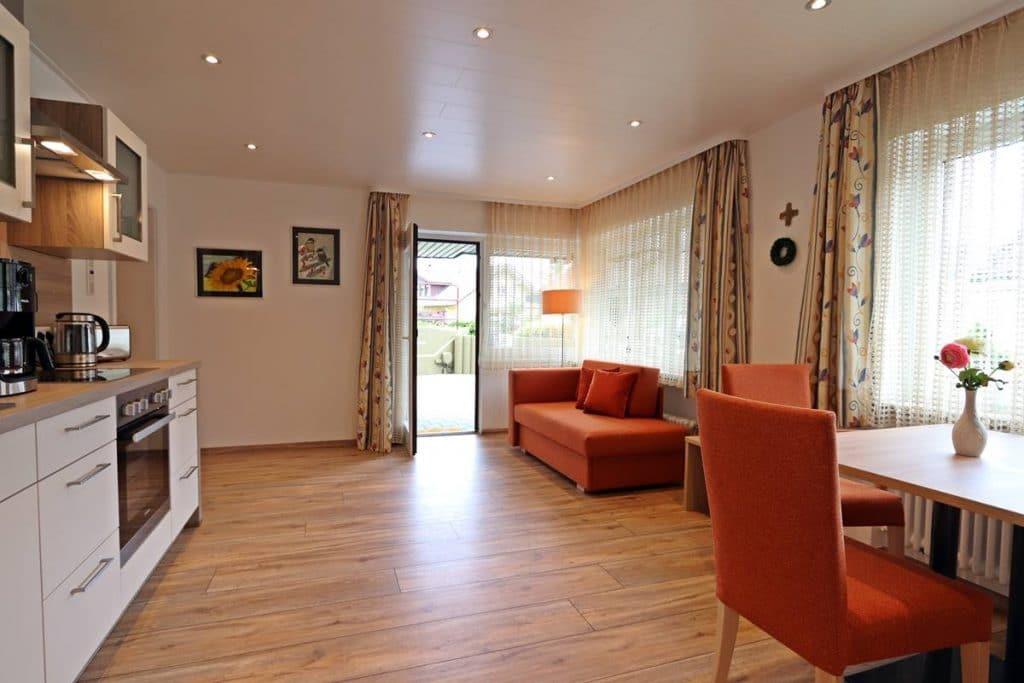 Küche der Ferienwohnung Rosalie mit Küchenzeile, Esstisch und Sofa
