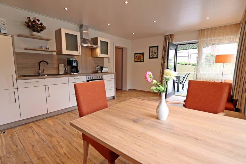 Moderne Küche mit Küchenzeile und Esstisch und Ausgang zur Terrasse
